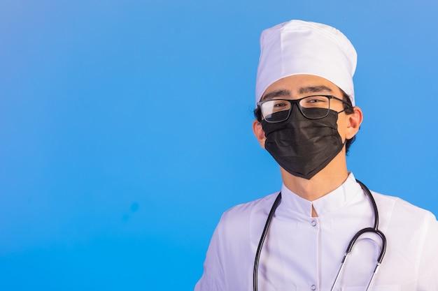 Dottore in uniforme medica bianca con stetoscopio e maschera facciale