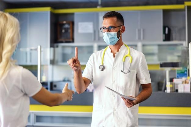 Dottore in uniforme sterile con maschera facciale su senza sospiro con la mano perché il paziente vuole stringergli la mano. in altra mano tiene la cartella con i risultati del test.