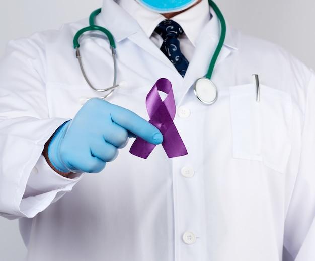 Dottore maschio in camice bianco e cravatta si erge e tiene un nastro di seta viola a forma di anello