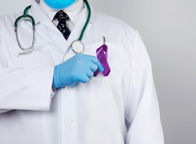 Dottore maschio in camice bianco e cravatta sta e tiene un nastro di seta viola