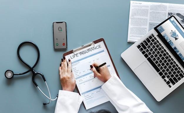 Dottore riempiendo un modulo di assicurazione sulla vita