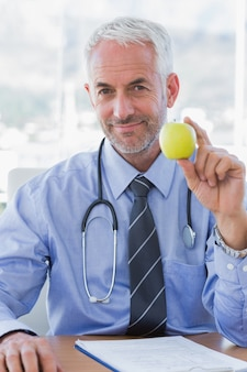 Dottore seduto dietro la sua scrivania in possesso di una mela