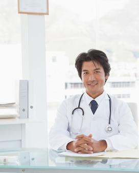 Dottore sorridente seduto alla sua scrivania