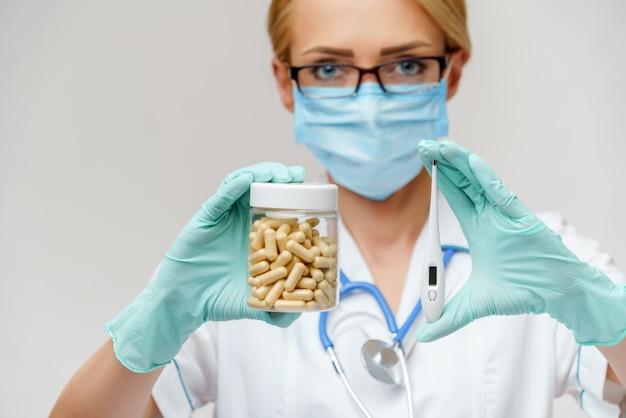 Dottoressa che indossa una maschera protettiva e guanti di gomma o in lattice e che tiene una lattina di medicina e termometro