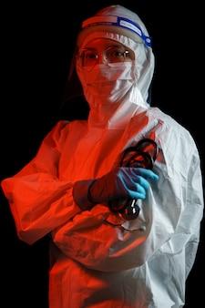 Dottoressa che indossa una tuta protettiva per il virus corona o la protezione covid-19. tuta hazmat, visiera, guanti, maschera, stetoscopio.