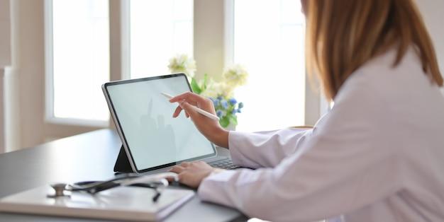 Dottoressa che lavora con tablet e scrivere su scartoffie in ufficio