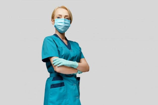 Dottoressa con stetoscopio indossando maschera protettiva e guanti in lattice