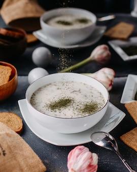 Dovga di yogurt con verdure all'interno del piatto bianco rotondo con pane pagnotte uova sul tavolo grigio