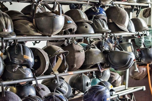 Dozzine di polverosi elmetti usati per cavalcare cavalli appesi su sbarre di ferro. cavallo trianing