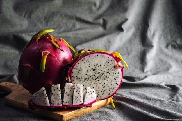 Dragon fruit organico o pitahaya sul piatto di legno con il fondo di struttura sgualcito
