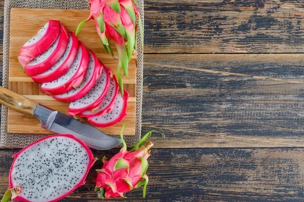 Dragon frutta con tagliere, coltello piatto giaceva sul tavolo di legno