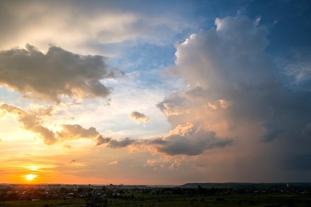 Drammatico tramonto sulla zona rurale con tempestose nuvole gonfie illuminate dal sole al tramonto arancione e cielo blu.