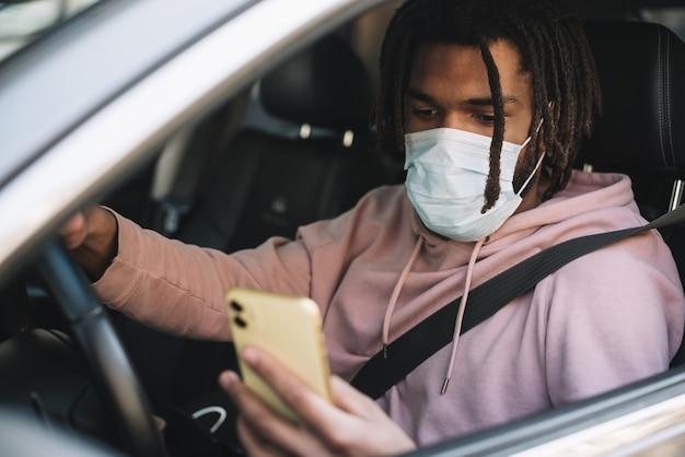 Driver afroamericano che esamina telefono