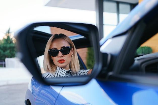 Driver della giovane donna che guarda nello specchietto retrovisore dell'auto, assicurandosi che la linea sia libera prima di girare.