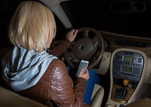 Driver femminile negligente che controlla il suo telefono durante la guida.