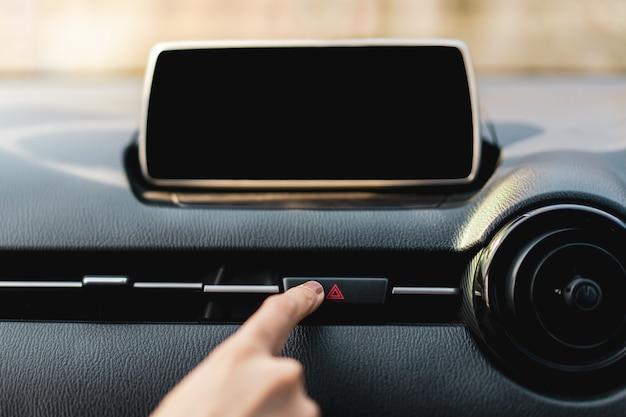 Driver premendo il pulsante di pericolo sul cruscotto di un'auto da vicino con schermata di infotainment vuota (schermata di intrattenimento all'interno di un'auto).