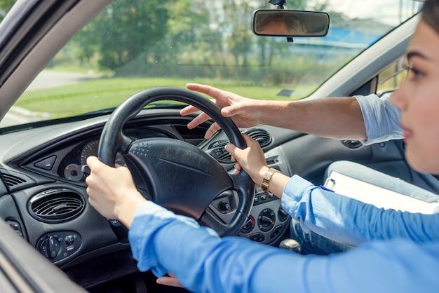 Driving school - la giovane donna guida un'auto con il volante, forse ha una guida