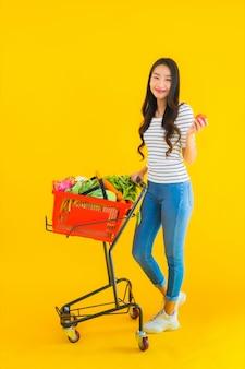 Drogheria di acquisto della giovane donna asiatica dal supermercato e dal carrello