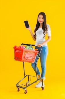Drogheria di acquisto della giovane donna asiatica dal supermercato