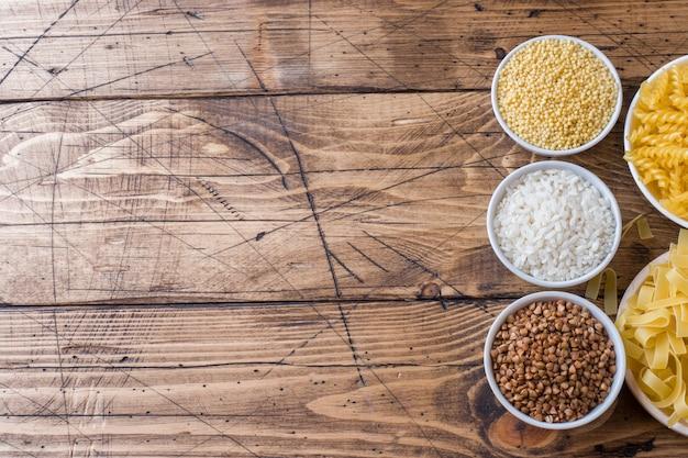 Drogheria di semole secche. grano saraceno e miglio della pasta di riso sulla tavola di legno.