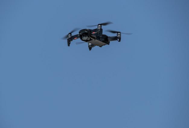 Drone che muove le pale che volano attraverso il cielo blu