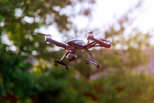 Drone con fotocamera cinema professionista che sorvola un parco in autunno colori