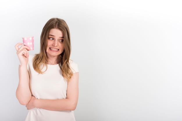 Dubbiosa giovane donna con la tazza di carta