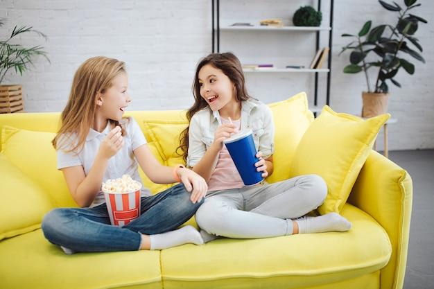 Due adolescenti felici e gioiosi si siedono sul divano giallo. si guardano e sorridono. le ragazze hanno una ciotola con popcorn e una tazza di coca cola.