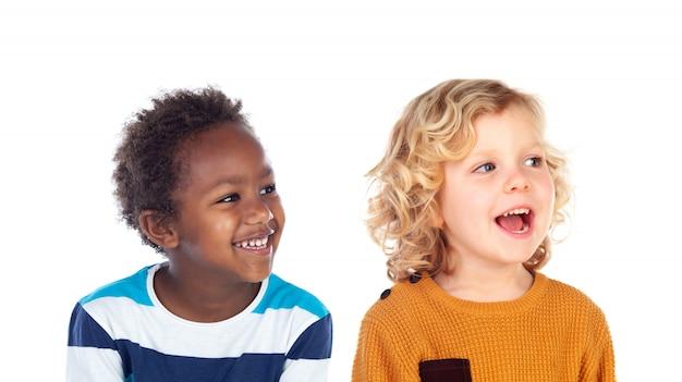 Due adorabili bambini di razze diverse isolati su uno spazio bianco