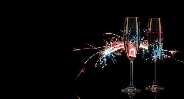 Due alti bicchieri di champagne in luci multicolori del bengala