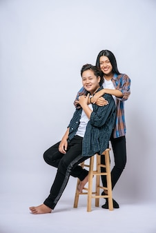 Due amanti delle donne afferrano un'altra spalla e si siedono su una sedia.