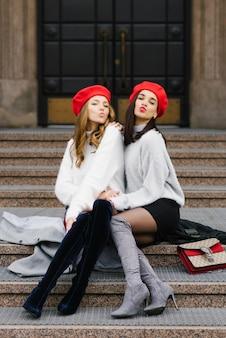 Due amiche alla moda in berretti soffiano baci seduti sui gradini della città. san valentino