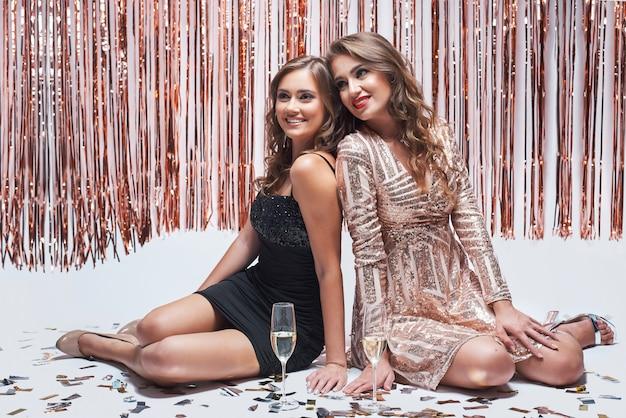 Due amiche che si siedono sul fondo bianco e che bevono champagne.