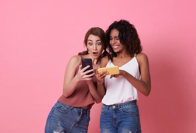 Due amiche felici che giocano e condividono i social media in uno smartphone.