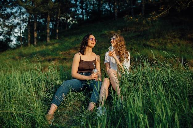 Due amiche felici si divertono, si siedono sull'erba, bevono cocktail in occhiali da sole, al tramonto, espressione facciale positiva, all'aperto