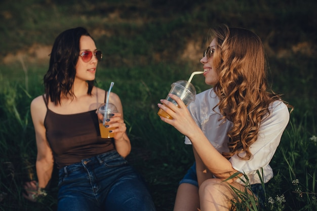 Due amiche felici sono allegre, sedersi sull'erba, bere succo d'arancia in occhiali da sole in camicia bianca e nera, al tramonto, espressione facciale positiva, all'aperto