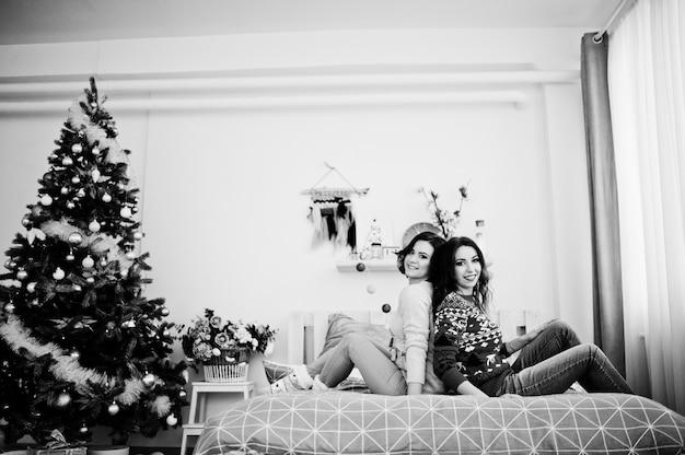 Due amiche indossano maglioni invernali divertirsi sul letto in camera con decorazioni di natale.
