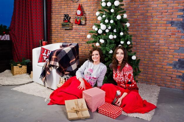 Due amiche indossano maglioni invernali seduti in camera con decorazioni di natale.