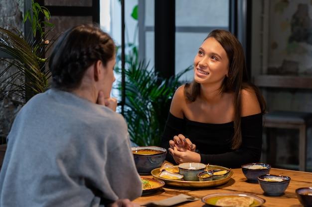 Due amiche parlano e mangiano in un moderno caffè