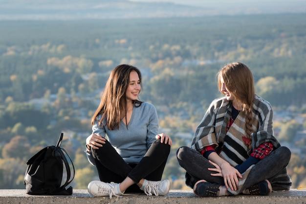 Due amiche sono sedute sullo sfondo della natura. viaggia con il migliore amico. vista frontale.