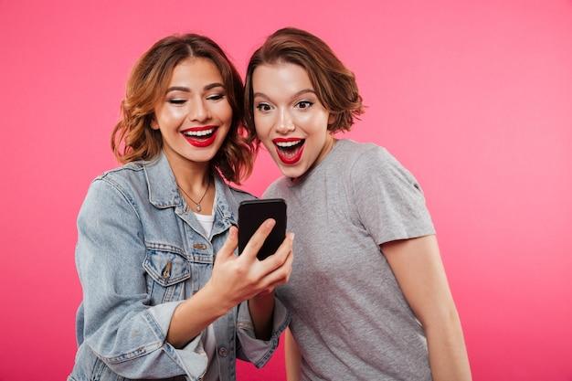 Due amiche sorridenti che per mezzo del telefono cellulare.