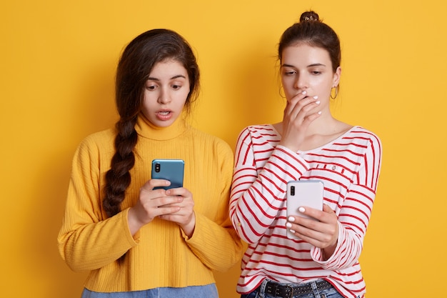 Due amiche tengono i telefoni in mano e guardano gli schermi con grandi occhi