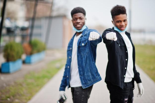 Due amici adolescenti africani al parco che indossano maschere mediche proteggono da infezioni e malattie da quarantena del virus coronavirus.