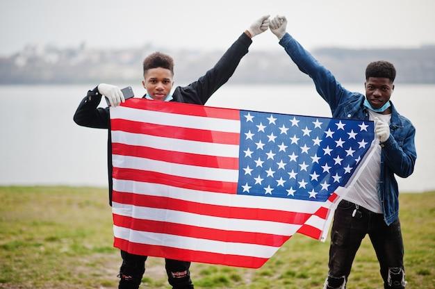 Due amici adolescenti africani con bandiera americana al parco indossando maschere mediche proteggono da infezioni e malattie da quarantena del virus coronavirus.