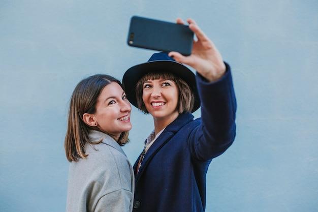 Due amici all'aperto con abiti eleganti prendendo un selfie con il telefono cellulare
