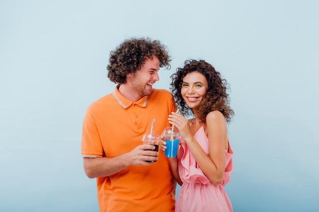 Due amici bevono il succo dal bicchiere di plastica