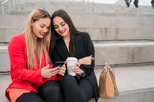 Due amici che utilizzano il loro telefono cellulare seduti all'aperto.