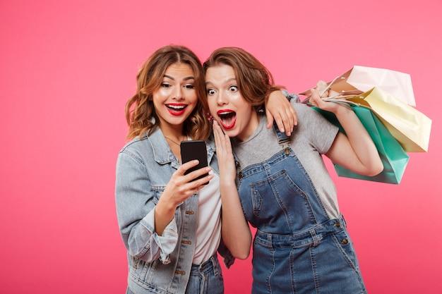 Due amici colpiti delle donne che tengono i sacchetti della spesa facendo uso del telefono cellulare.