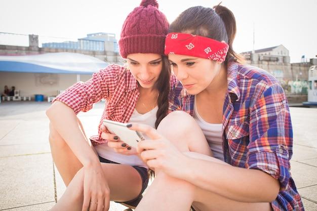 Due amici della ragazza dell'adolescente che hanno divertimento sulla sera d'estate all'aperto. fanno lo skateboard
