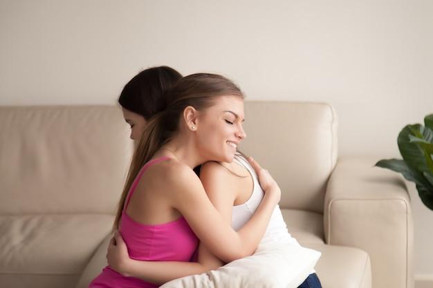 Due amici delle giovani donne che abbracciano sul sofà